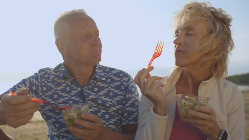 Elderly wife and husband eating tasty salad having picnic on sea beach. Happy active senior couple relaxing on lake shore, enjoying healthy snack and chatting spending leisure time together outdoors | Shutterstock HD Video #1055368292