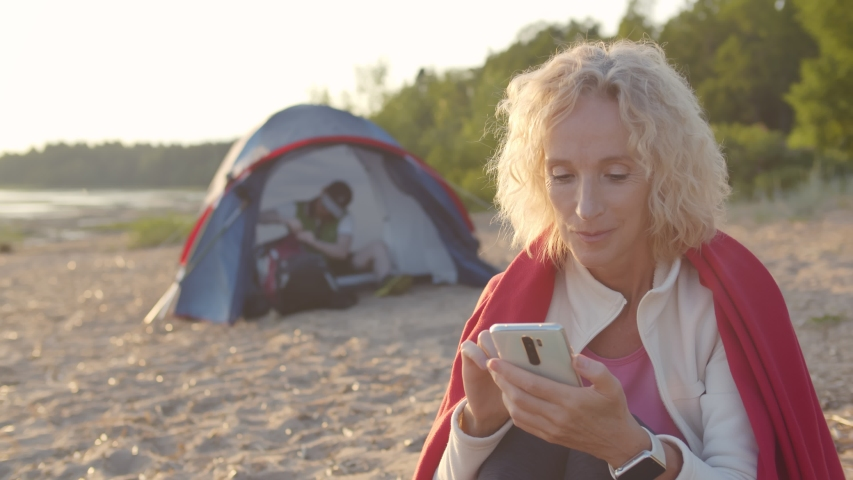 Portrait of mature woman covered with blanket sitting on beach sand surfing internet on smartphone during camp trip. Young man sitting in tent on background | Shutterstock HD Video #1055368295