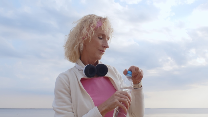 Senior woman drinking water after exercising on summer beach. Side view of thirsty aged female drinking water from bottle after jogging on sea shore. Fitness, sport and healthy retirement concept | Shutterstock HD Video #1055368304