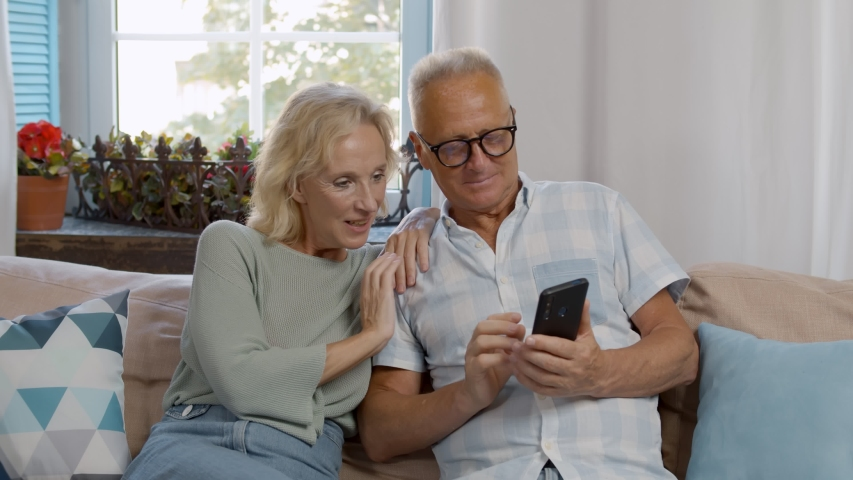 Portrait of smiling senior couple resting on comfortable sofa and watching video or shopping online on mobile phone spending free time together at home | Shutterstock HD Video #1055368313