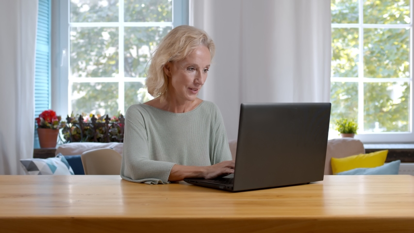 Portrait of mature woman sitting ant table and her husband hugging her from behind browsing internet together purchasing vacation tour or shopping online | Shutterstock HD Video #1055368319