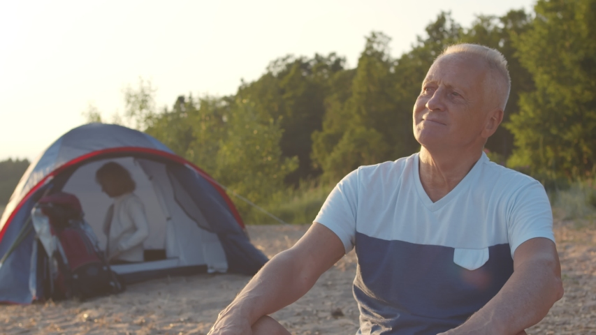 Portrait of senior happy man relaxing sitting on beach sand enjoying camping trip. Woman making bed in tent on background. Elderly couple camping on sea shore. Happy retirement and travel concept | Shutterstock HD Video #1055368325