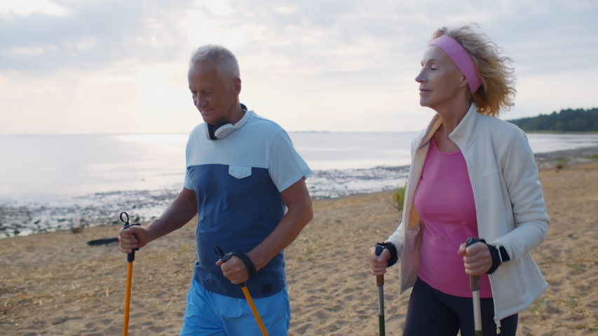 Happy active aged couple trekking along coastline on sandy beach in morning. Portrait of sporty mature man and woman nordic walking with hiking sticks on lake shore | Shutterstock HD Video #1055368331
