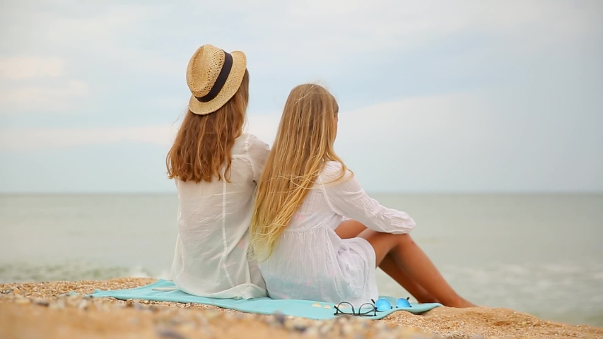 Beautiful young mother and pretty teen daughter sitting on the beach at sunrise | Shutterstock HD Video #1055368667
