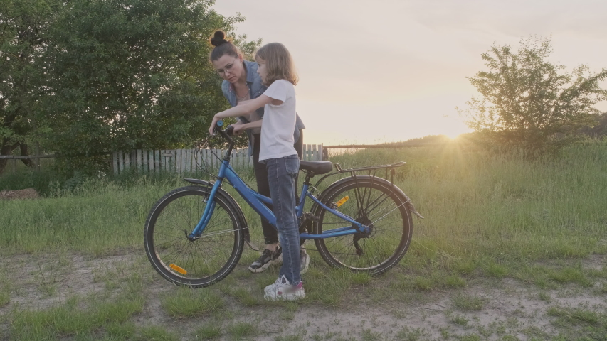 Mom teaches kid daughter ride bike, girl rides bicycle on country road, sunset natural landscape background. Happy family childhood active lifestyle, childish success concept. High quality 4k footage | Shutterstock HD Video #1055368694
