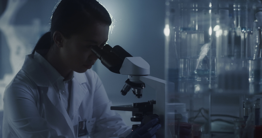 Young female scientist working after hours. Using microscope in futuristic laboratory | Shutterstock HD Video #1055369033