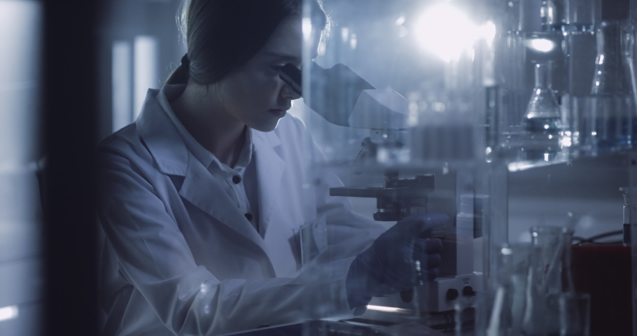 Young female scientist working after hours. Using microscope in futuristic laboratory | Shutterstock HD Video #1055369039
