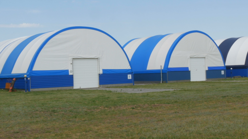 Exterior view of a series of hangars for small aircraft at an airfield outside the city. | Shutterstock HD Video #1055369315