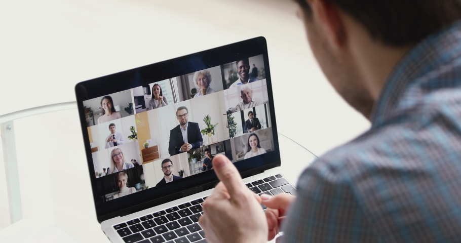 Concept of distant communication using laptop and internet connection, video call conferencing application. Diverse people young and old take part at group videocall activity, view over male shoulder Royalty-Free Stock Footage #1055370323