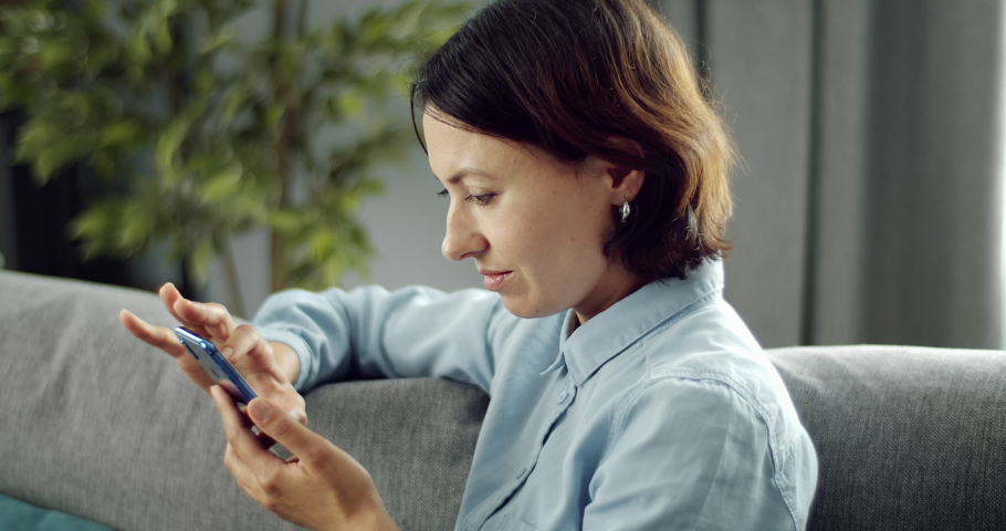 Side view of mature woman with dark hair spending leisure time at home and using smartphone. Charming lady in domestic outfit sitting on couch with modern gadget. | Shutterstock HD Video #1055370476