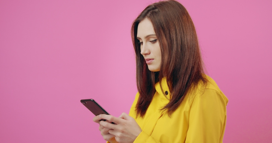 Side view of happy woman with dark hair texting message on smartphone over pink background. Young girl in yellow raincoat chatting with friends online. | Shutterstock HD Video #1055370482