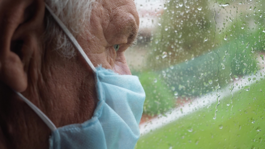 Portrait closeup thoughtful old man with wrinkles in protecting mask, looks sadness out of window at street when it rains, drops rolled down glass. Isolation in covid-19 pandemic at home or hospital | Shutterstock HD Video #1055370692