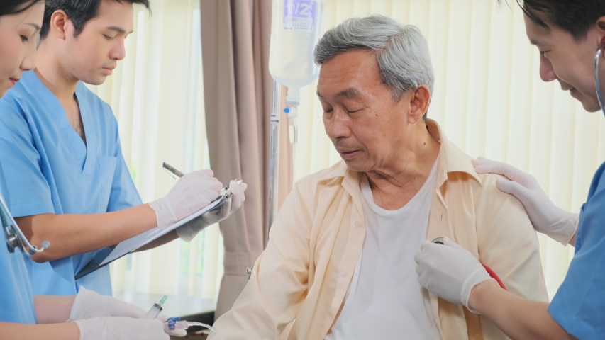 Asian medical team doctors nurse examining and checking Asian elderly male patient, health care staff take note on clipboard and pressure check with conversation in hospital.  Royalty-Free Stock Footage #1055376923