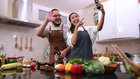 Happy young married couple cooking together in the kitchen. Young couple using smartphone for video call in the kitchen.