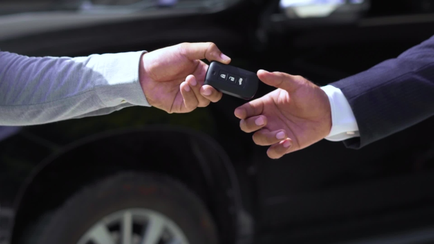 Car salesman finishing up dealing car and shaking hands. Businessman giving car key contract buying black car in vehicle showroom gallery. slow motion shot.