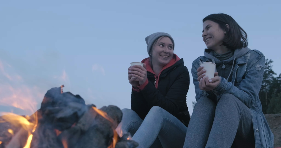 Two Cute Girls Sitting on Log on Seashore. Before them is Burning Bonfire. Bright Flame. Girls Drink Hot Tea from White Cups. Couple. Cute to each other. Smiling. Look at each other. In love. Camping   Shutterstock HD Video #1055386589