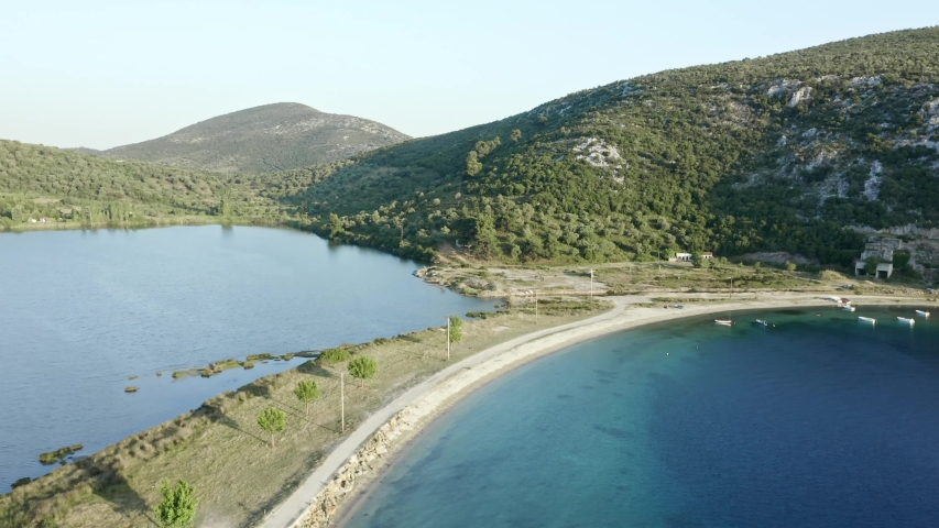 Aerial footage of sea bay and lake with narrow striped beach at Porto Koufos, Chalkidiki peninsula, Greece. | Shutterstock HD Video #1055386937
