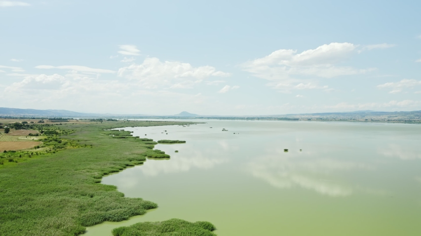 Aerial footage of lake with sky reflection on water. Koroneia green lake, Greece. | Shutterstock HD Video #1055386940
