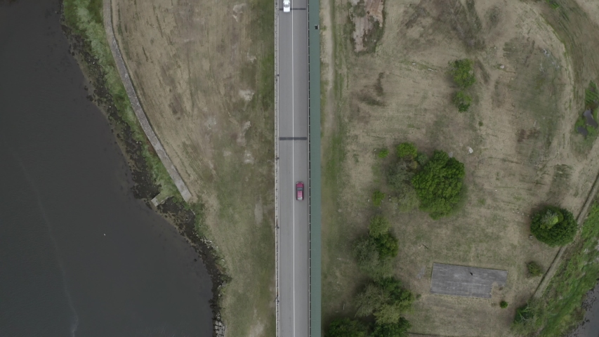 aerial view of a cars riding on a bridge over a river, shooting from a drone | Shutterstock HD Video #1055387117