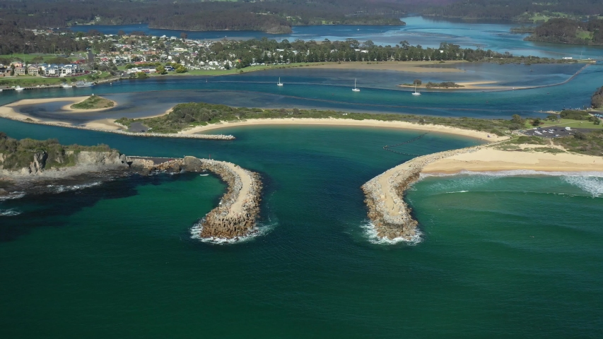 Aerial drone pullback reveal of Wagonga Head and Wagonga Inlet at Narooma on the New South Wales South Coast, Australia, on a sunny day   | Shutterstock HD Video #1055387888