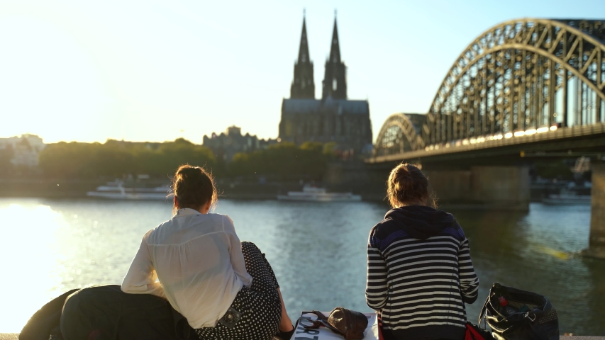 Two female tourists sit near the bridge in Cologne on a sunny day. Germany | Shutterstock HD Video #1055388377