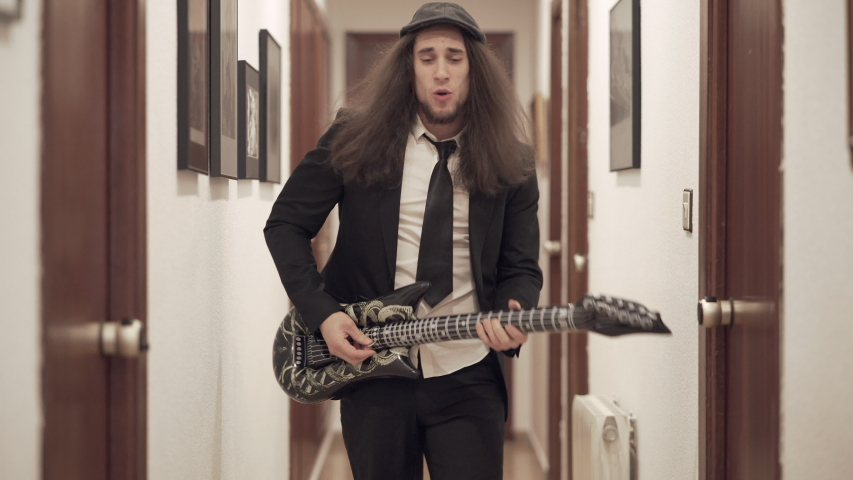 Young long-haired man in suit plays inflatable toy guitar in apartment