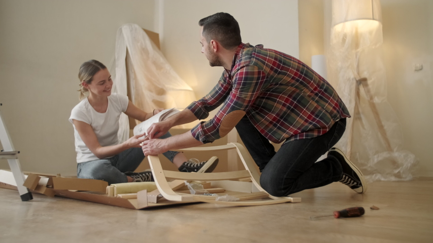 Happy Smiling Couple Collects Furniture As a Team, Girl Reads Instructions, Boy Holds Chair Details. Moving to New Apartment, Young Family Assemble Furniture. Royalty-Free Stock Footage #1055389862
