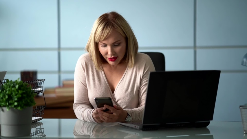 Female office worker is using social media by smartphone at working place   Shutterstock HD Video #1055391650