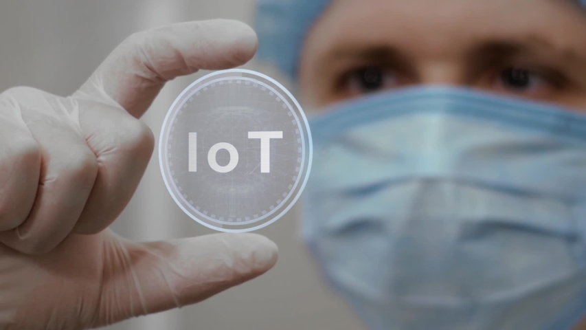 Doctor looks at innovative holographic projection with text IoT. Male scientist in medical mask conducting technological research on hologram. Concept of futuristic medicine, device of future science   Shutterstock HD Video #1055392469