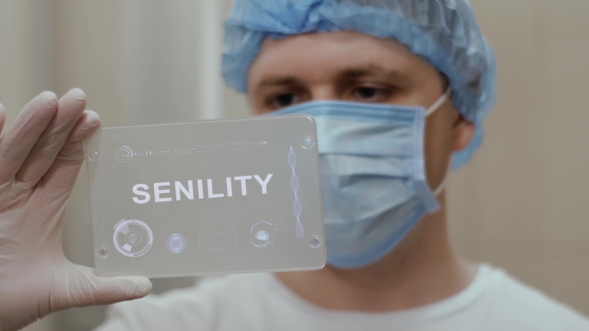 Doctor in face mask interacts futuristic hud screen tablet with text Senility. Medical concept of future technology. Futuristic doctor with modern medical care gadget   Shutterstock HD Video #1055392484