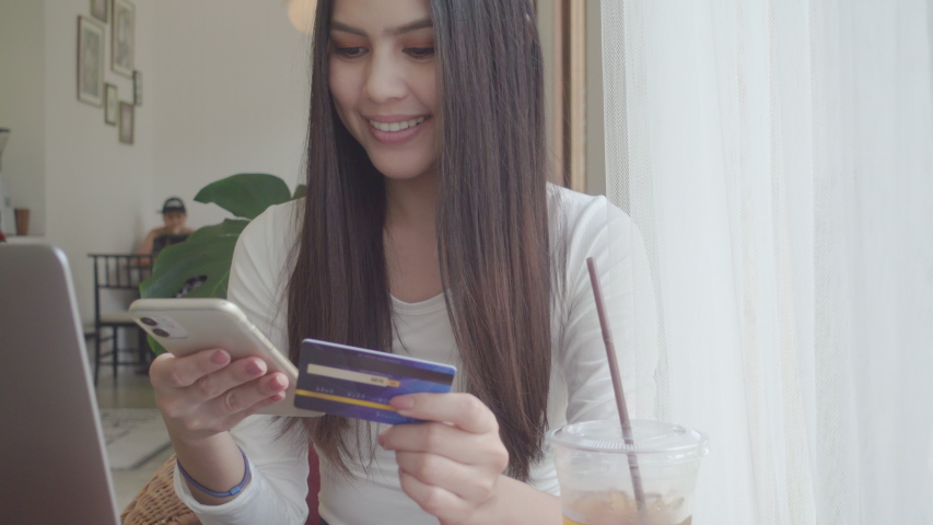A young beautiful woman is using credit card for shopping online  in coffee shop    Shutterstock HD Video #1055393507