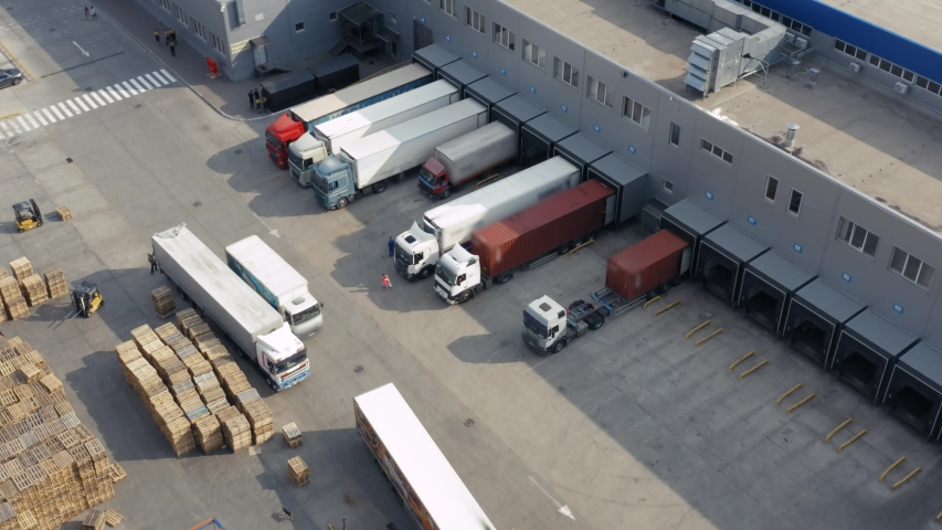 Aerial view of a semi trucks with cargo trailers standing on warehouses ramps for loading/unloading goods on the big logistics park with loading hub