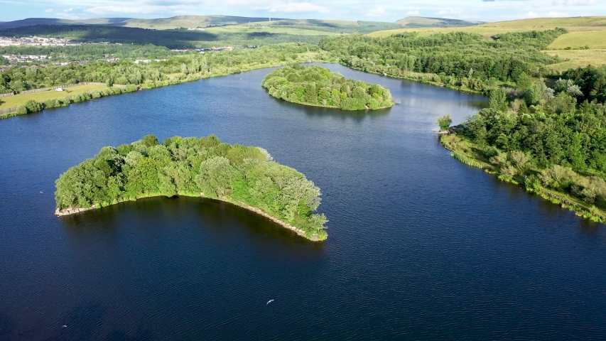Aerial drone view of a lake with small islands in a rural setting (Bryn Bach Park, Tredegar, South Wales, UK)