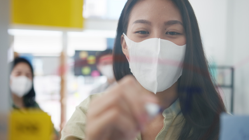 Asia young businesspeople discussing business brainstorming meeting working together sharing data and writing glass wall with medical face mask back at work in office. Life and work after coronavirus. Royalty-Free Stock Footage #1055397731
