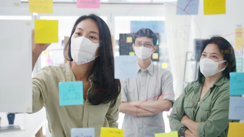 Asia young businesspeople discussing business brainstorming meeting working together sharing data and writing glass wall with medical face mask back at work in office. Life and work after coronavirus. Royalty-Free Stock Footage #1055397734