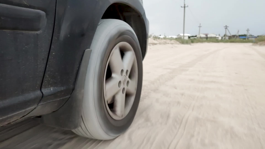 Car suspension works on a sand . car wheel vibration in slow motion. tire on car driving on hard road in summer