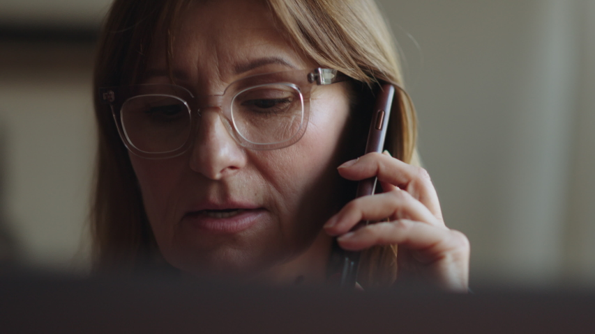 Portrait of an adult tired woman talking on the phone and working on a laptop. Mature woman freelancer speaks on a smartphone at a computer and looks at the monitor. Remote work freelancer at home Royalty-Free Stock Footage #1055401259