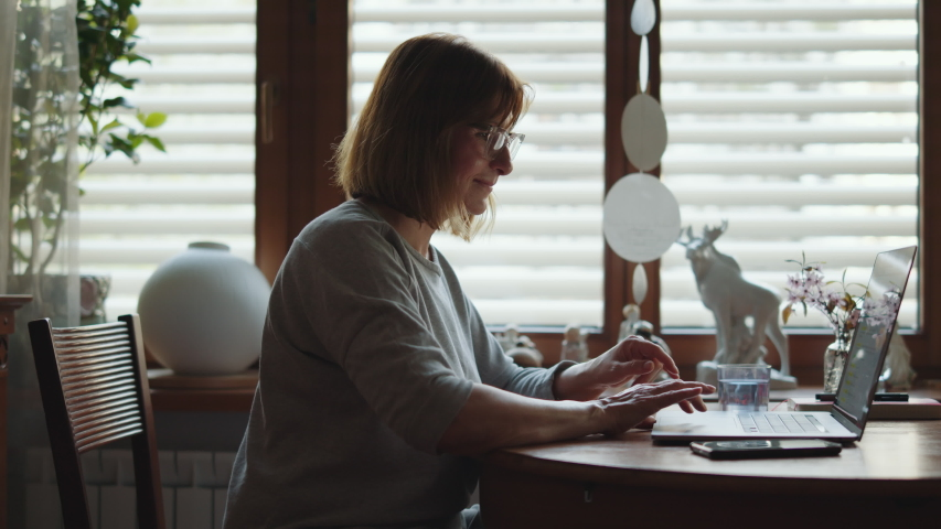 Portrait of an adult joyful woman working on a laptop. Mature happy woman freelancer at the computer and looking at the monitor. Remote work freelancer at home workplace. Close-up. Royalty-Free Stock Footage #1055401298