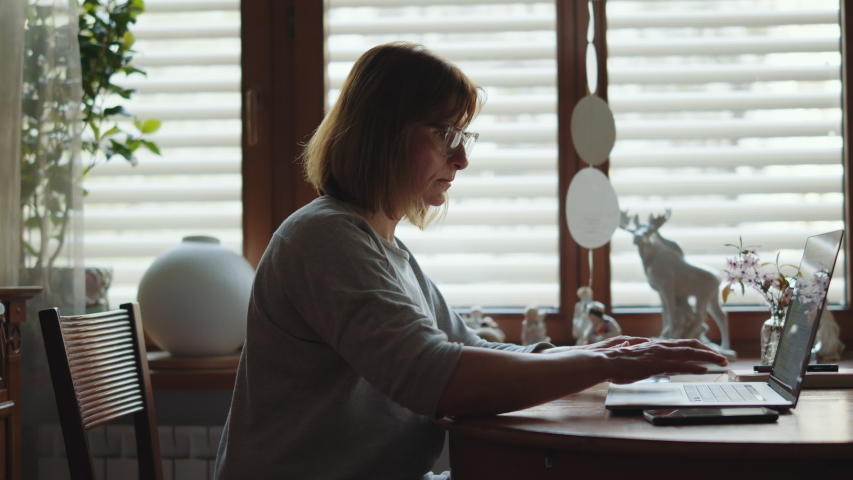 Portrait of an adult woman working on a laptop. Mature woman freelancer at a computer looking at the monitor. Remote work freelancer at home workplace. Royalty-Free Stock Footage #1055401301