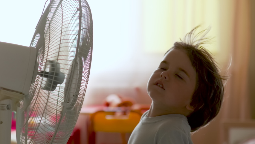 Boy Standing in Front of Fan. Child Enjoying Cool Wind From Electric Fan at Home at Summer Vacation. Suffer From Heat High Temperature in Front of Ventilator Cooling Herself With Electric Fan-Cooler. Royalty-Free Stock Footage #1055404376