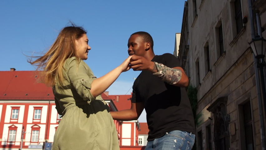 Black man and white woman dancing in the street. Lovely interracial couple dancing on a city street. Salsa and Latin American dances, social dances