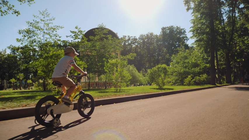 A child rides a bicycle in a city park. Happy boy riding bike, having fun outdoors on nature. Active sport family leisure. | Shutterstock HD Video #1055406233
