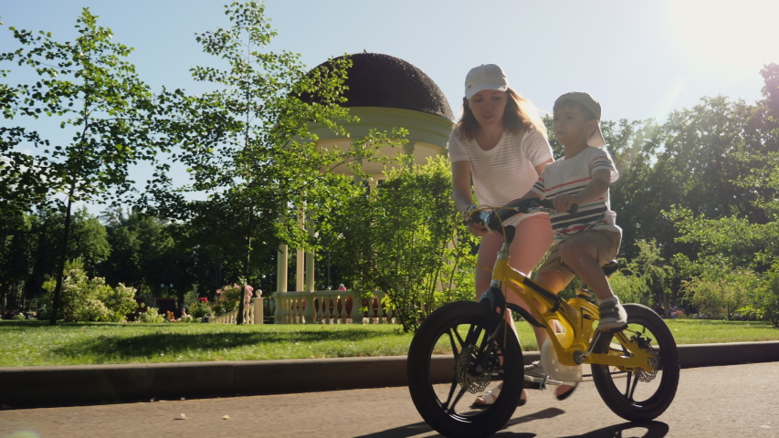 Mom teaches her little son to ride a bicycle in the city park, slow-motion. Happy family moments. Time together mother and son. | Shutterstock HD Video #1055406245