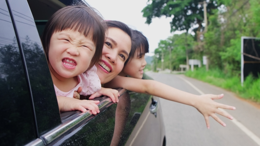 Asian family having relax vacation on holiday together. Mother and children sit and playing on back rear seat open car window to face air outside. Young daughters and mom feeling happy with smile face