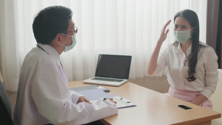 Asian female patient coming to examination room and consult health problem to male doctor sitting in room. Medic man, woman wearing protective surgical face mask preventing covid virus pandemic.