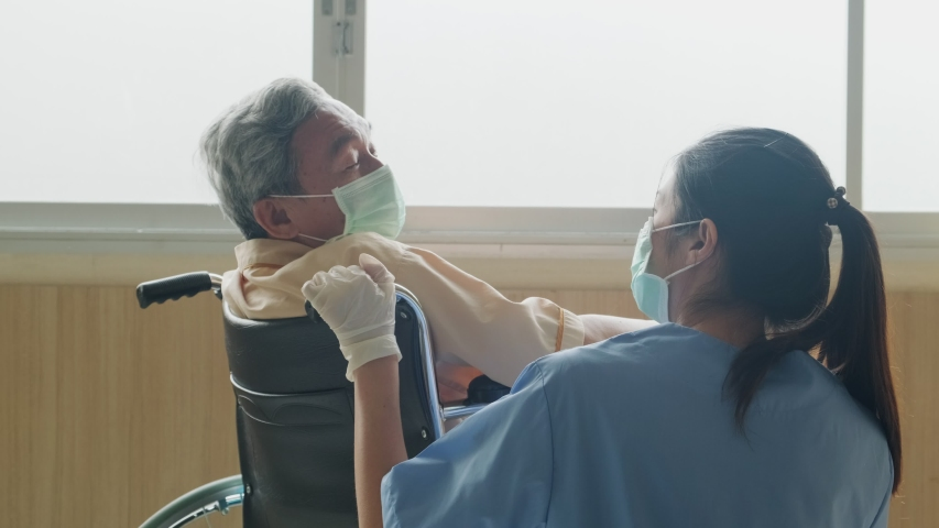 Asian nurse taking care of mature male patient sitting on wheelchair in hospital. Young woman and old man wearing surgical face mask for protection of covid 19 pandemic. Girl smile to elderly man. Royalty-Free Stock Footage #1055407649