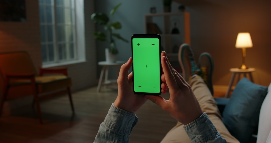 Close up shot of guy lying on couch at night, holding a smartphone with chroma key mock up green screen - technology, connections, communications concept 4k video template