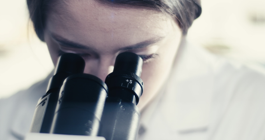 Modern laboratory. Female scientist working with microscope. Biohazardous samples | Shutterstock HD Video #1055408732