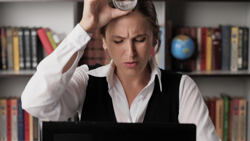 Sweating female in white wet shirt and plain look working at laptop, he is hotly muffled and uncomfortable, drinks water and pours it on himself. Heat, excitement, deadline, nervous tension concept