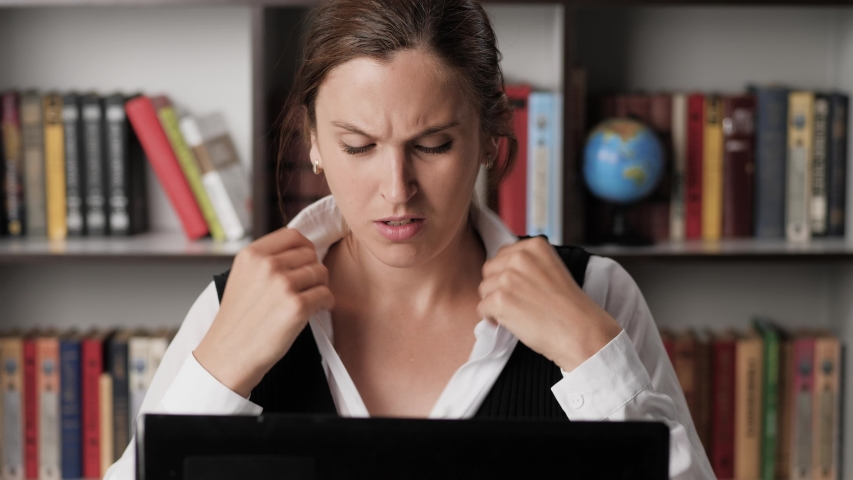 Sweating woman in wet shirt and plain look is working at computer, she is hotly muffled and uncomfortable, drinks water and is worried. Heat, excitement, deadline, nervous tension concept. Close-up
